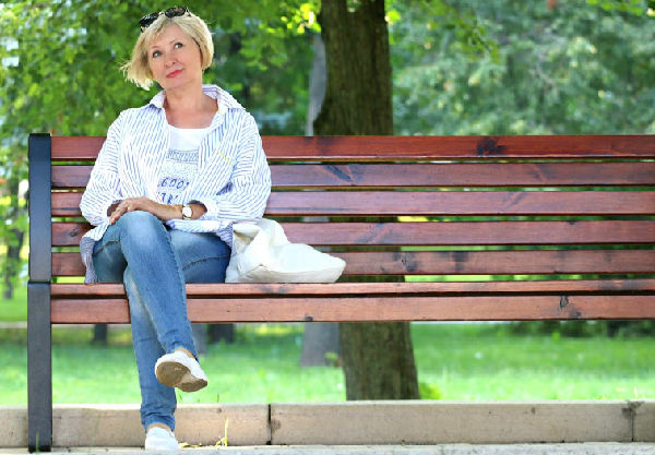 woman sitting on a bench in a park thinking about how she is unique.
