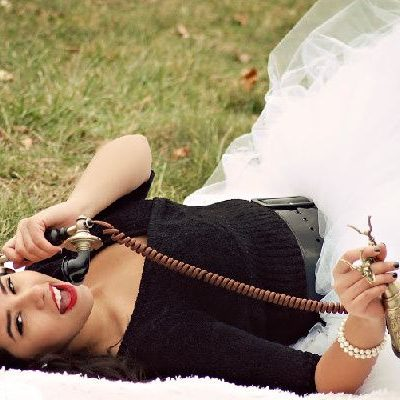 Woman lying on the grass with an old phone
