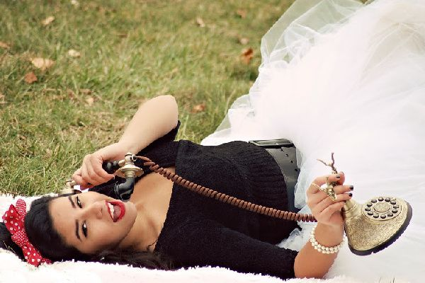 Woman with dark hair lying on the grass talking on a vintage phone.